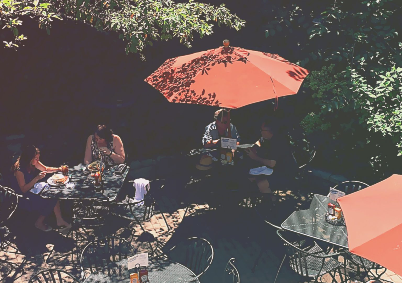 Overhead view of restaurant outdoor patio where several people are sitting at tables