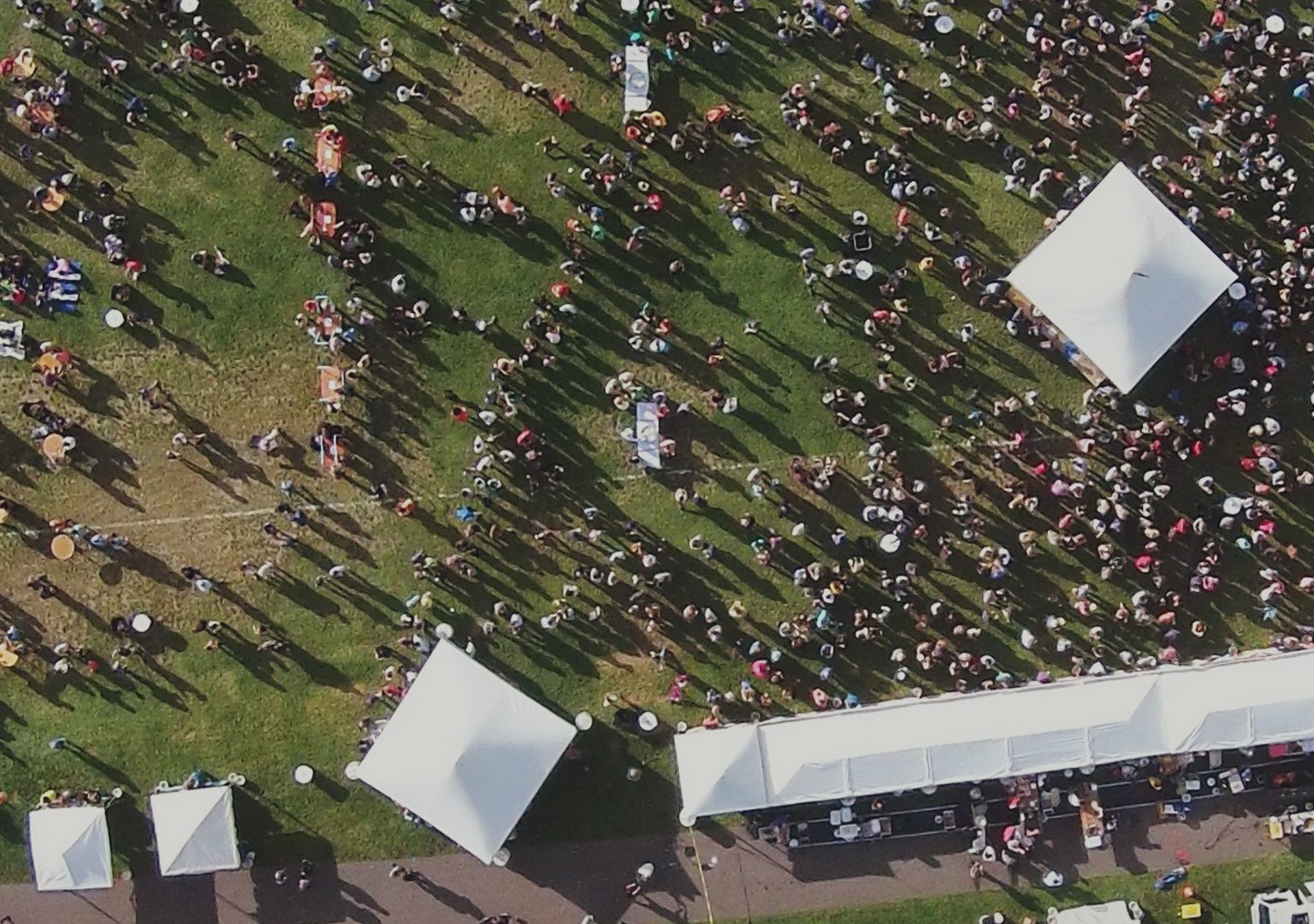 Aerial view of crowds and food tents in grassy area at Yum Yum Fest
