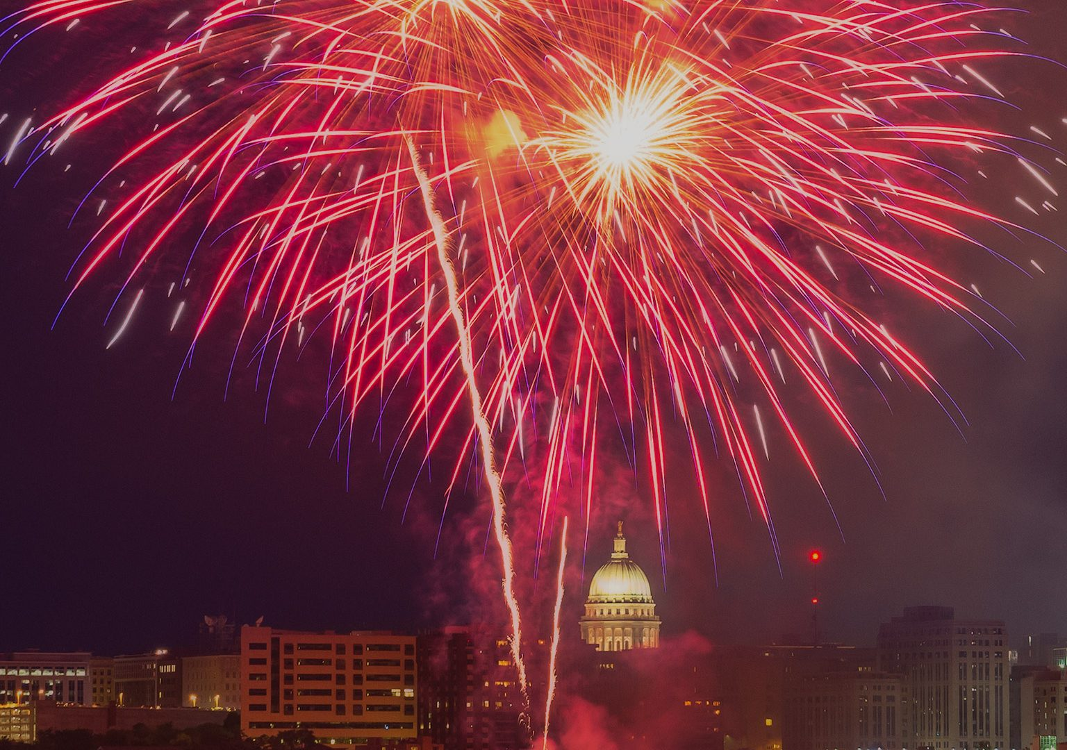 View from across a lake of fireworks erupting over the Madison, WI skyline at night
