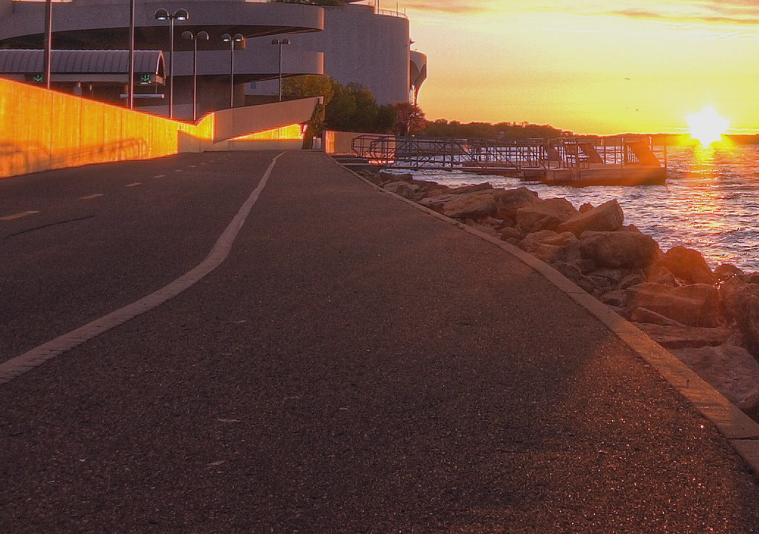 Paved bike path on lakeshore in the foreground with sun rising over horizon in the distance