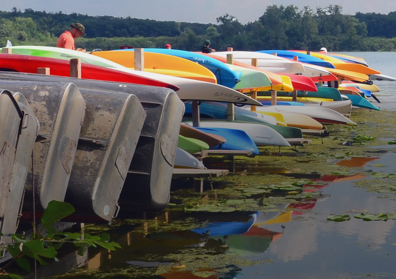 Row of colorful boats stored near dock overlooking Lake Wingra