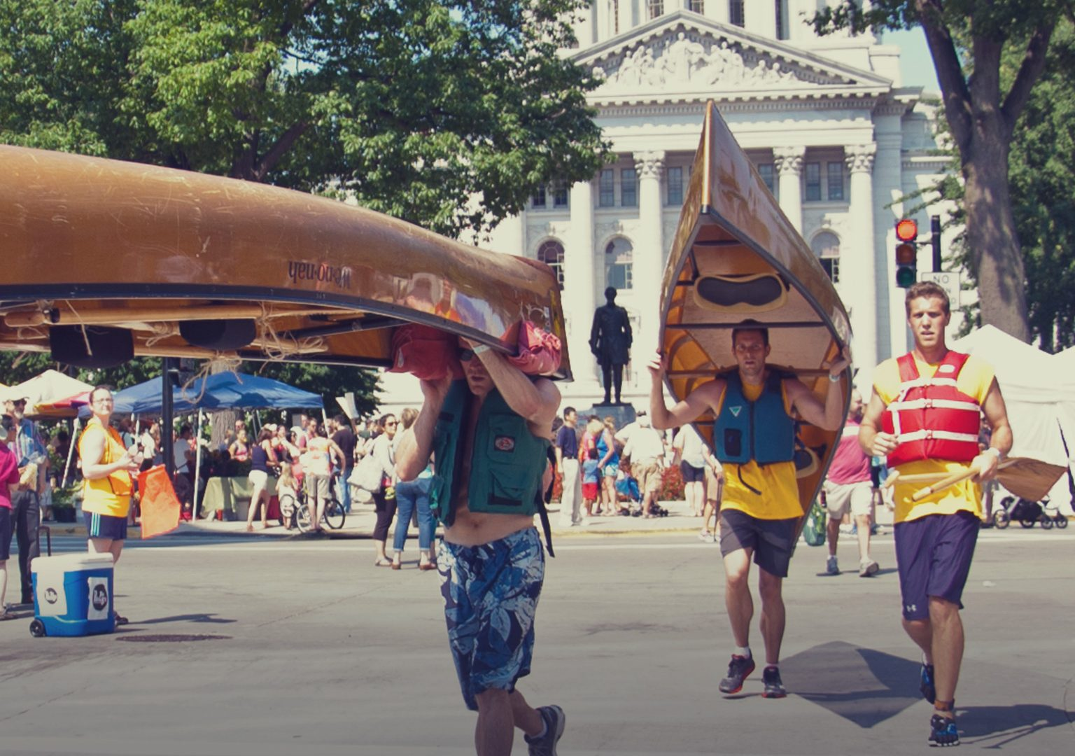 Race participants carrying canoes over their heads running across street with Capitol building in background