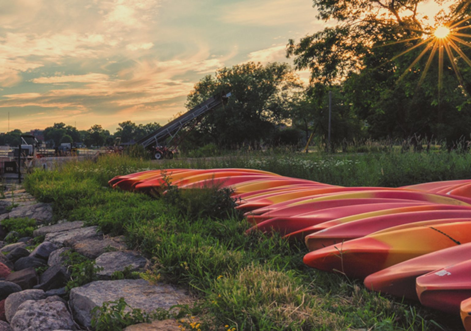 Canoes line the shore of Lake Mendota as the sun sets behind grove of trees in background