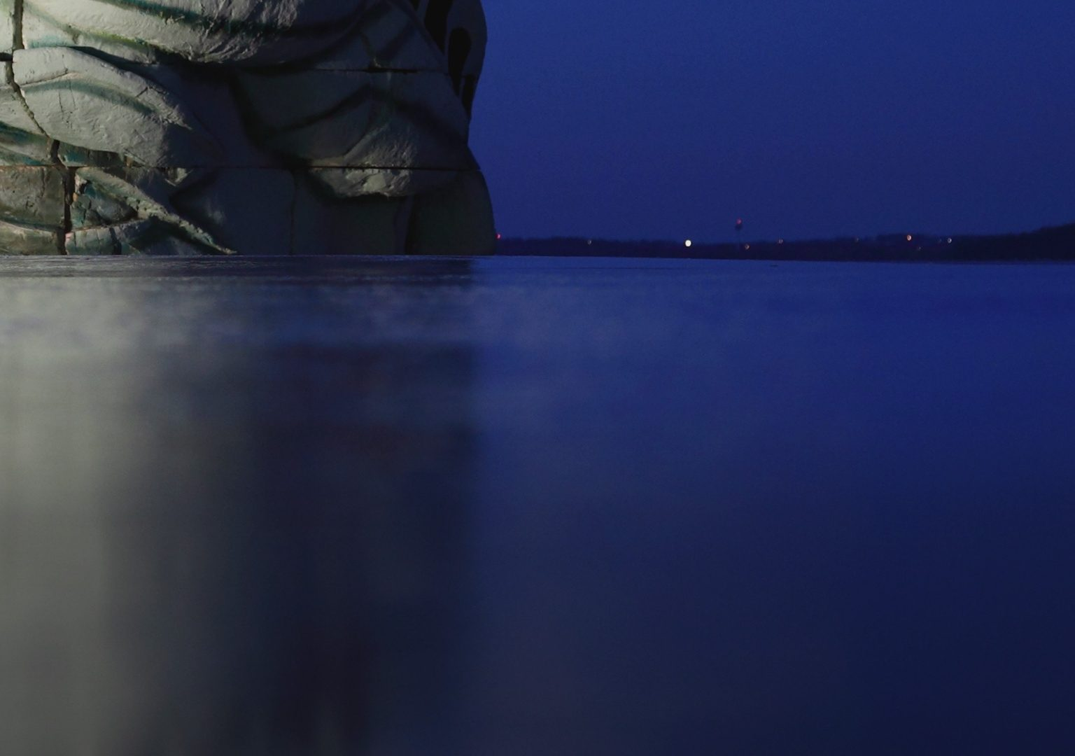 Replica of the top of the head of Statue of Liberty sits atop a frozen lake at night