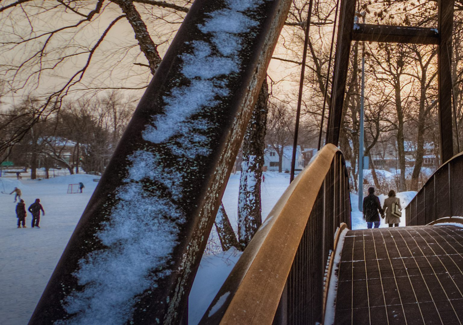 Long shot of two people from the other side of a metal bridge in a snow-covered park at dusk