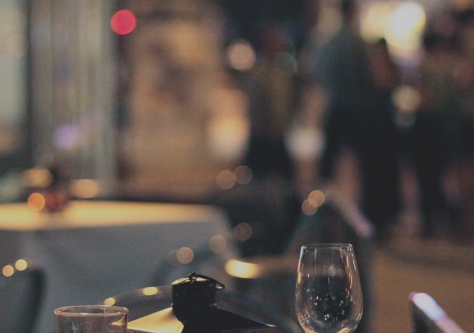 Restaurant table outdoors at nighttime with lantern and wine and water glasses in foreground, bus stop and people on sidewalk can be seen in background
