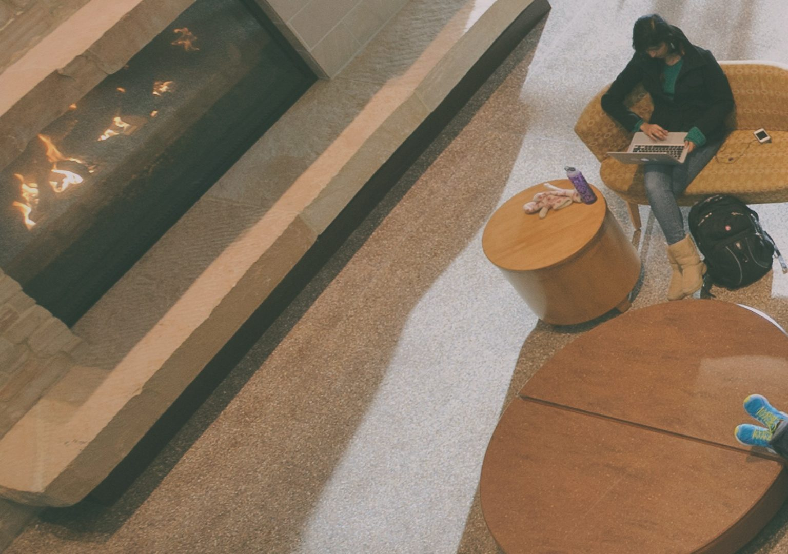 Overhead view of fireplace and tables occupied by people inside of Union South
