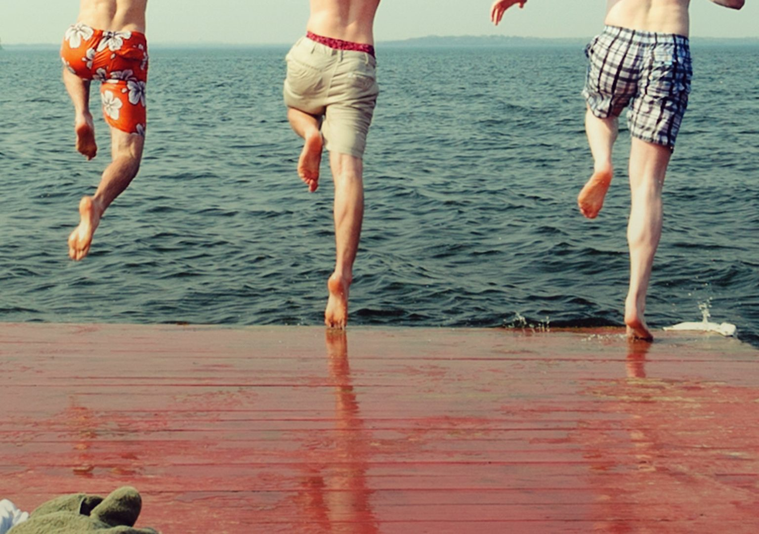 Action shot of three young men about to jump off edge of dock into lake