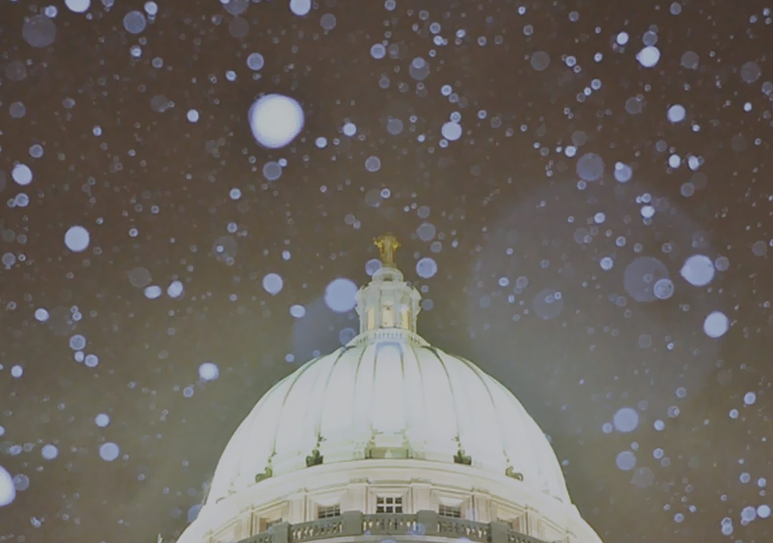Close-up of Wisconsin State Capitol dome at night with snow falling